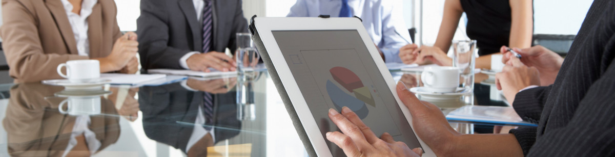 Close Up Of Businesswoman Using Tablet Computer During Board Meeting Around Glass Table